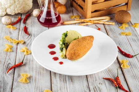 Restaurant served chicken Kiev cutlet with mashed potato and lingonberry sauce