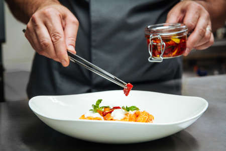 Chef hand cooking pasta penne with mozzarella cheeze and sun-dried tomatoes in a white plate