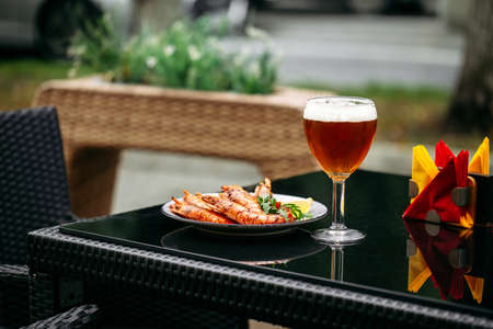 Side view on golden beer in a glass with langoustines on the glass table outdoor