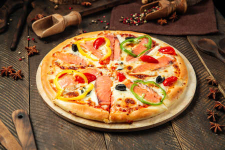 Side view on pizza with salmon and bell pepper on the wooden table