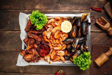Top view on assorted beer fried snack with shrimp mussels and chicken on the wooden table