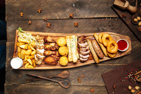 Top view on fried salty beer snacks on the wooden board with sauces Фото со стока