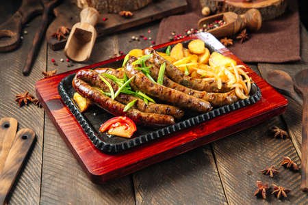 Side view on grilled sausages with potatoes on the wooden table Фото со стока