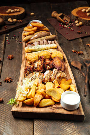 Side view on fried salty beer snacks on the wooden board with sauces Фото со стока - 155694887