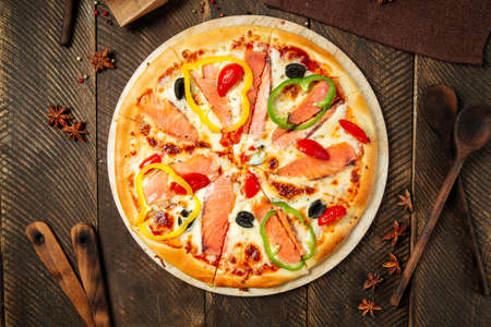 Top view on pizza with salmon and bell pepper on the wooden table Фото со стока - 155694411
