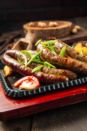 Closeup on grilled sausages with potatoes on the wooden table