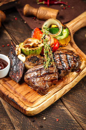 Closeup on grilled beef steaks with vegetables and sauce on the wooden board