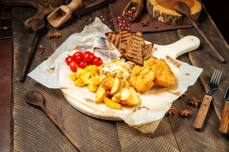 Russian snack set with herring and vegetables on the wooden board