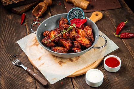Side view on roasted garnished chicken in a pan on the wooden table Фото со стока