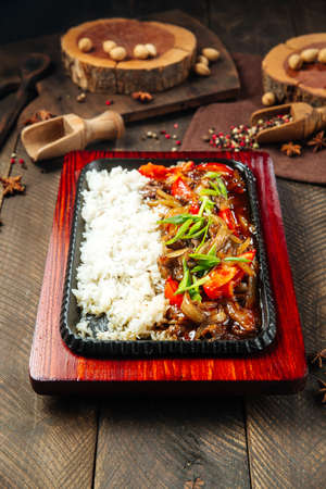 Side view on roasted beef with vegetables and rice in cast iron pan