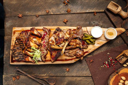 Top view on assorted roasted meat set on the wooden board Foto de archivo