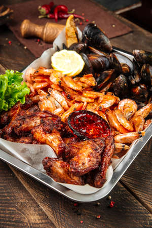 Closeup on assorted beer fried snack with shrimp mussels and chicken on the wooden table Фото со стока - 155694361