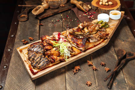 Side view on assorted roasted meat set on the wooden board Фото со стока - 155694120