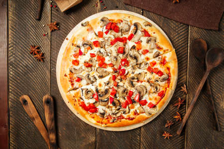 Top view on pizza with mushrooms and tomatoes on the wooden table Фото со стока - 155695090