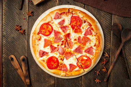 Top view on pizza with ham and tomatoes on the wooden table