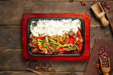 Top view on roasted beef with vegetables and rice in cast iron pan Фото со стока