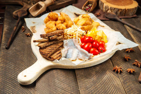 Side view on russian snack set with herring and vegetables on the wooden board