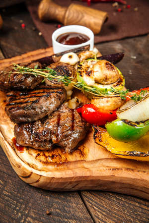 Closeup on grilled beef steaks with vegetables and sauce on the wooden board Фото со стока - 155702445