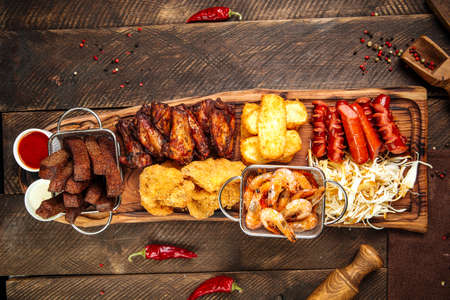 Top view on fried salty beer snacks on the wooden board with sauces Фото со стока - 155851525