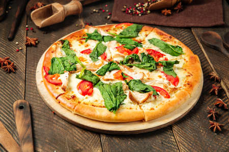 Side view on pizza napoli with spinach and tomatoes on the wooden table