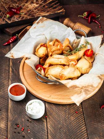 Closeup on russian snacks mini fried pies chebureki wth sauce on the wooden table Фото со стока