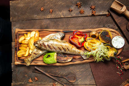 Top view on grilled fish with vegetables on the wooden board Фото со стока - 155775092
