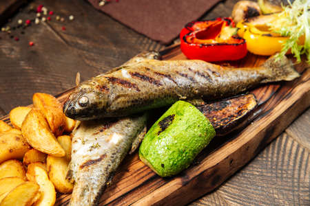 Closeup on grilled fish with vegetables on the wooden board Фото со стока