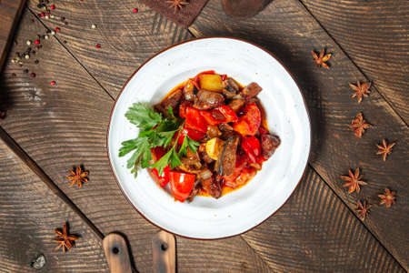 Top view on warm salad with eggplant beef and tomatoes