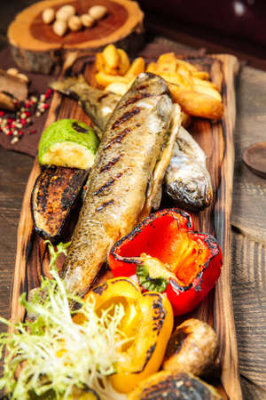 Side view on grilled fish with vegetables on the wooden board Фото со стока - 155775078
