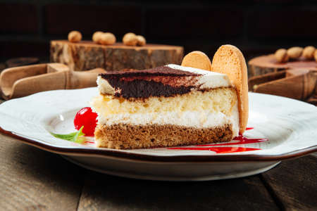 Closeup side view on tiramisu cake with berry sauce on the wooden table