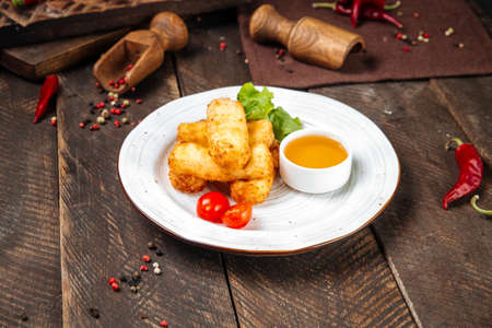 Side view on deep fried mozzarella cheese with sauce on the wooden table