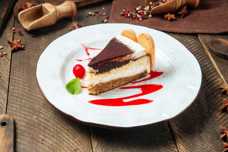 Side view on tiramisu cake with berry sauce on the wooden table Фото со стока - 155775094