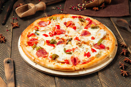 Spicy mexicano pizza with jalapenos on the wooden table