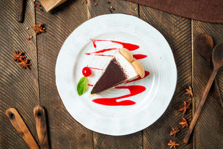 Top view on tiramisu cake with berry sauce on the wooden table