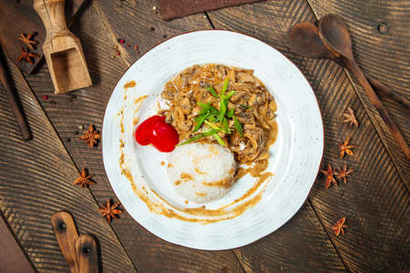 Top view on beef stroganoff with rice on a wooden table