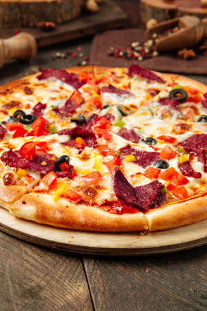 Closeup on pizza with smoked beef and vegetables on the wooden table Фото со стока - 155774237