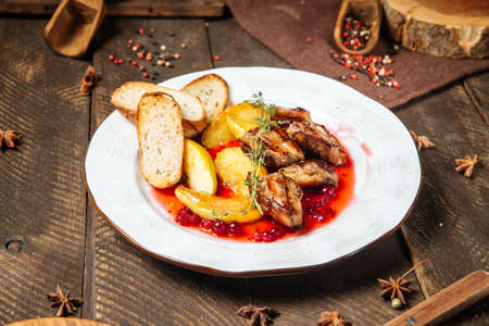 Side view on roasted chicken with potatoes toasts and lingonberry sauce