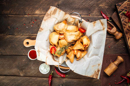 Top view on russian snacks mini fried pies chebureki wth sauce on the wooden table Фото со стока - 155774353