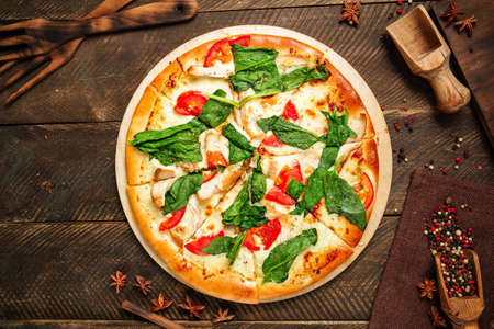 Top view on pizza napoli with spinach and tomatoes on the wodoen table Фото со стока - 155774315
