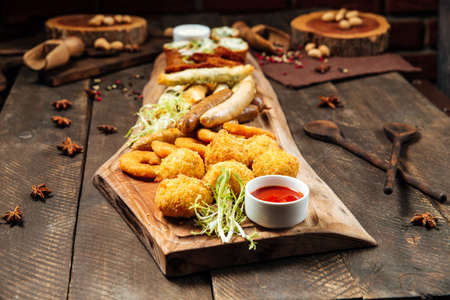 Side view on fried salty beer snacks on the wooden board with sauces Фото со стока