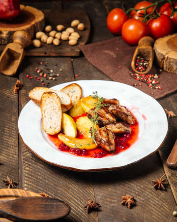 Side view on roasted chicken with potatoes toasts and lingonberry sauce Фото со стока - 155774559