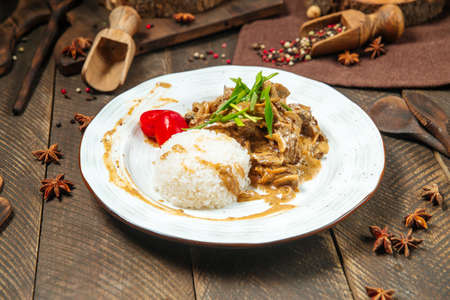 Side view on beef stroganoff with rice on a wooden table