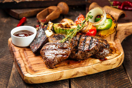 Side view on grilled beef steaks with vegetables and sauce on the wooden board