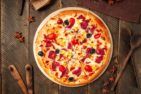 Top view on pizza with smoked beef and vegetables on the wooden table Фото со стока