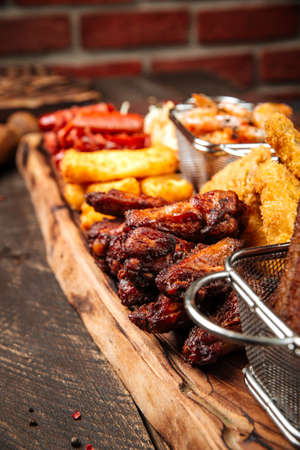 Closeup on fried salty beer snacks on the wooden board with sauces