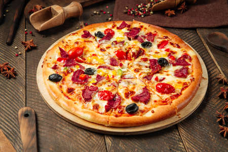 Side view on pizza with smoked beef and vegetables on the wooden table Фото со стока - 155774939