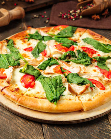 Closeup on pizza napoli with spinach and tomatoes on the wodoen table Фото со стока