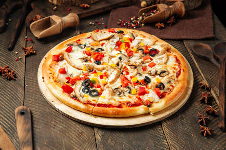 Side view on chicken pizza with mushrooms and vegetables on the wooden table Фото со стока