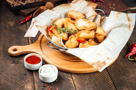 Side view on russian snacks mini fried pies chebureki wth sauce on the wooden table Фото со стока