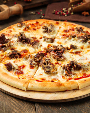 Closeup on pizza with beef meat under the cheese on the wooden table Фото со стока - 155840946
